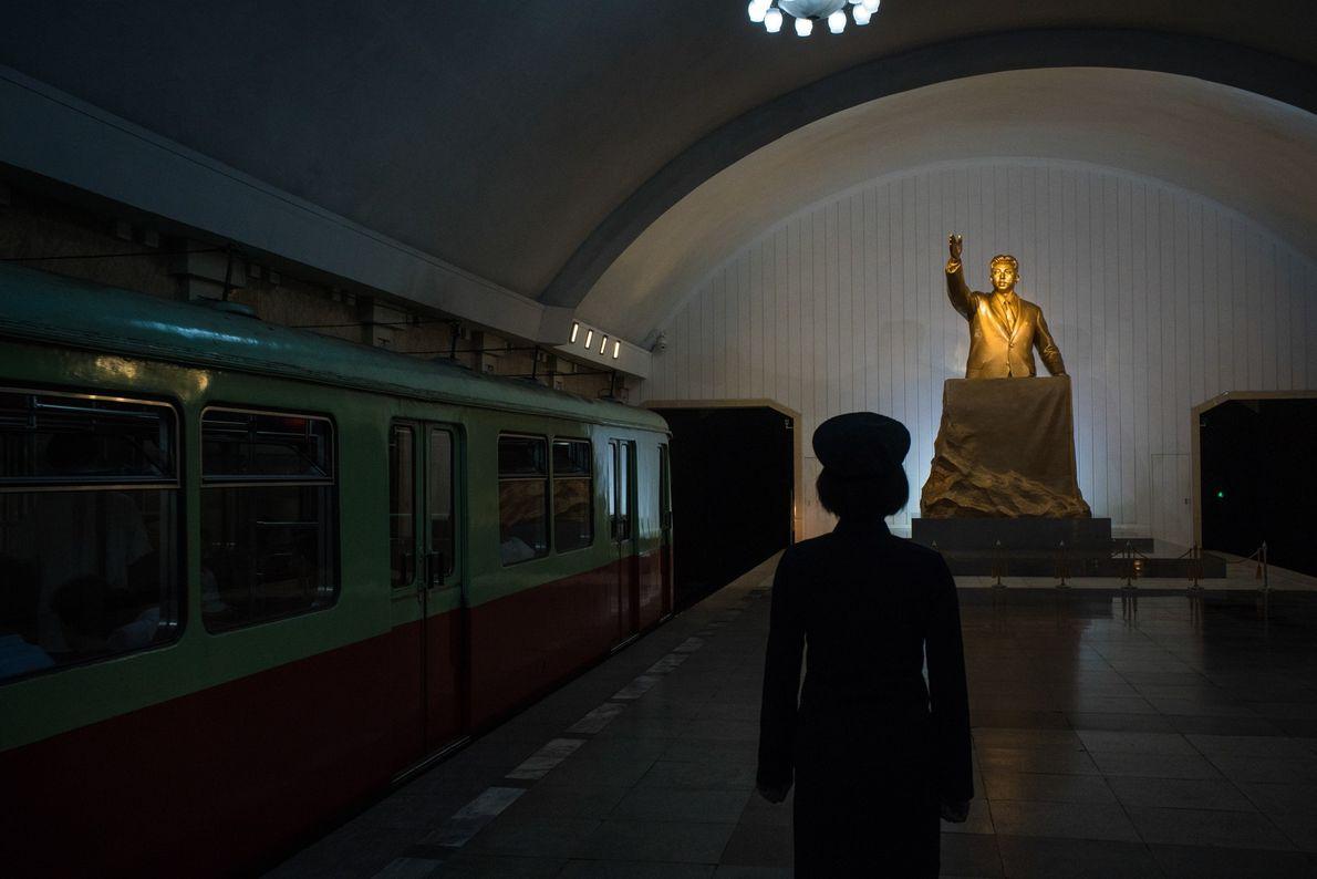 Um chefe de estação ferroviária diante de uma estátua de Kim Il Sung, numa estação de ...