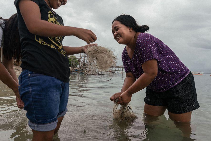 Uma mulher filipina limpa as redes abandonadas para vender, sendo reciclada, posteriormente, no estrangeiro.