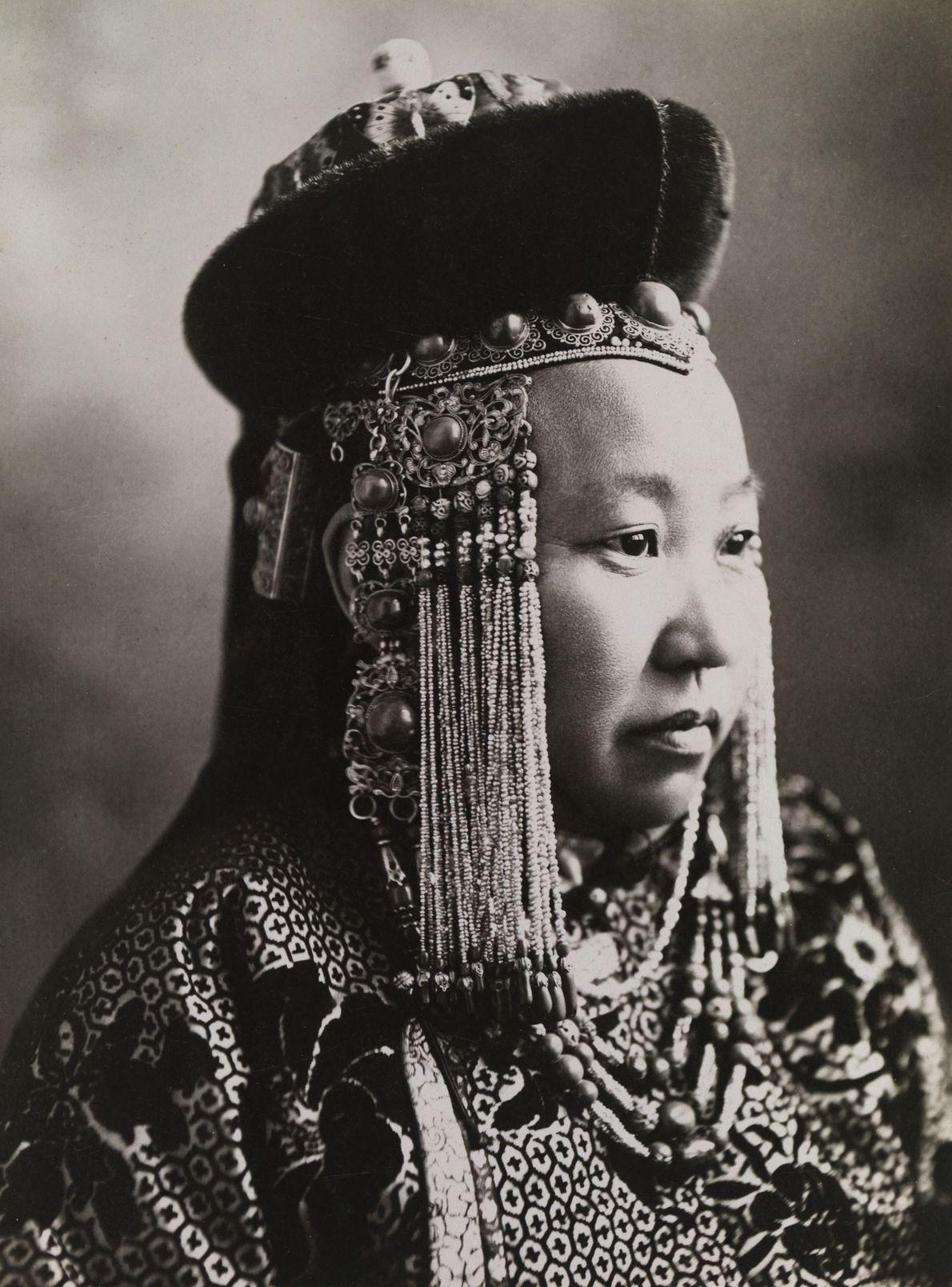 Uma princesa mongol veste um traje da corte completo, incluindo um ornamento tradicional para a cabeça.