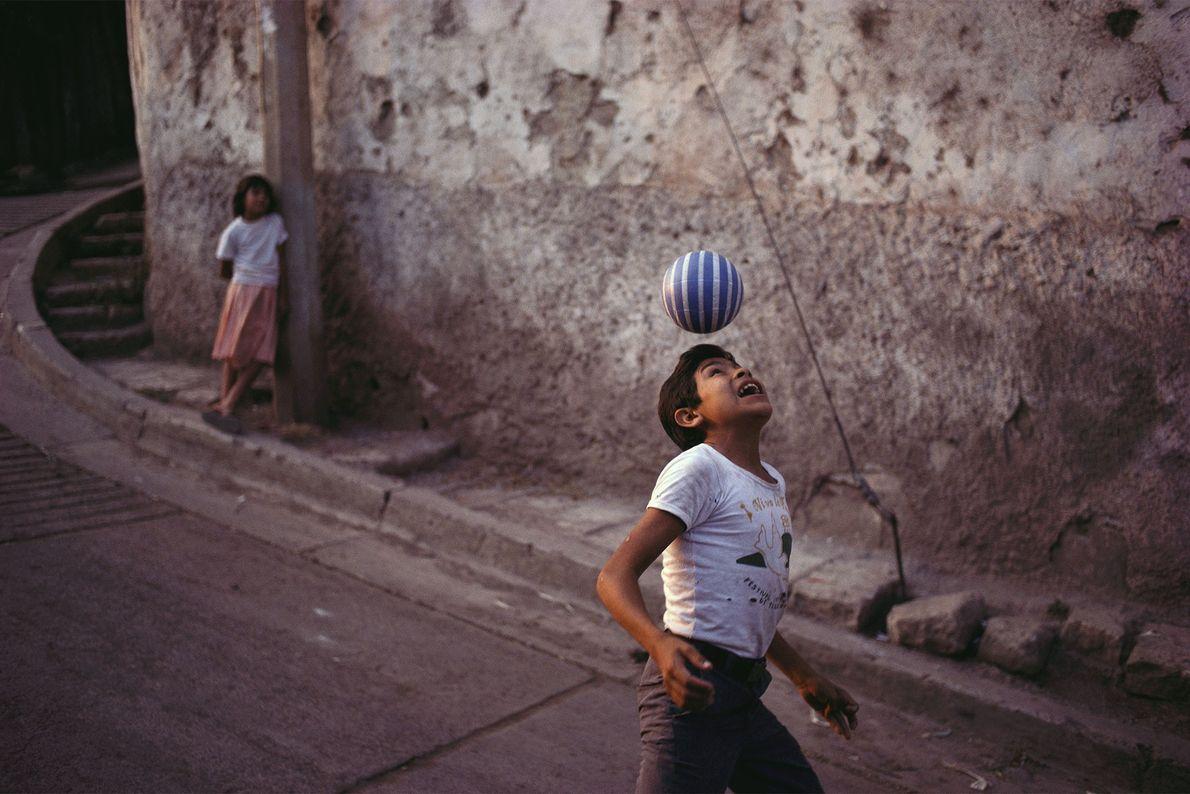 Um rapaz treina as suas aptidões futebolísticas ao longo de uma rua.
