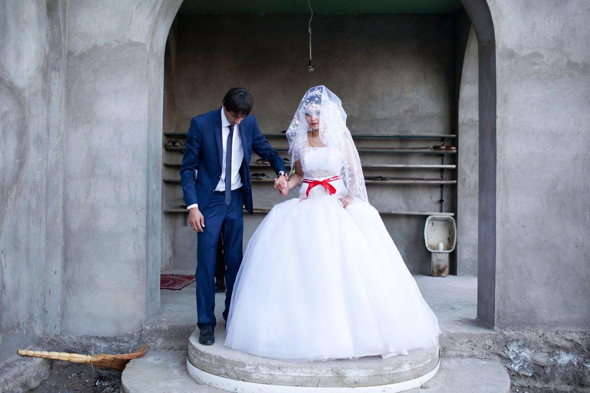 Imagem de uma noiva e de um noivo a pousarem em frente a uma mesquita