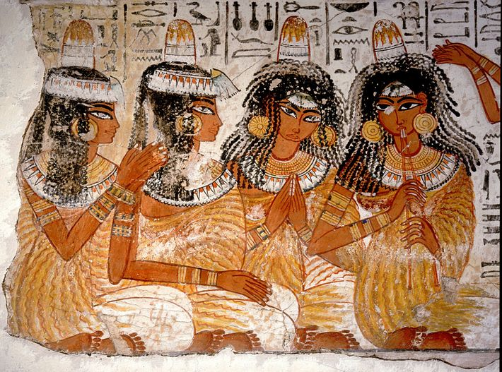 Mulheres representadas num banquete de há 3300 anos com objetos em forma de cone na cabeça. ...