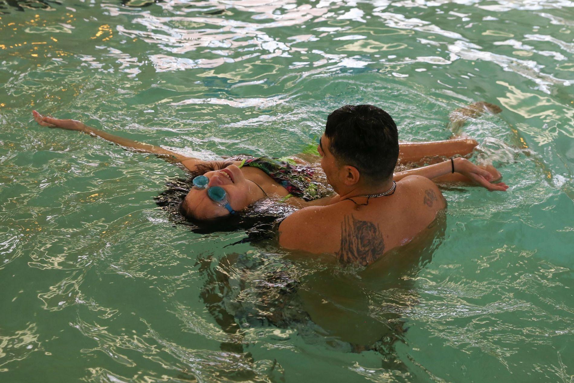 Agustin Muñoz ensina a sua filha Lola a flutuar de costas na piscina de um hotel.