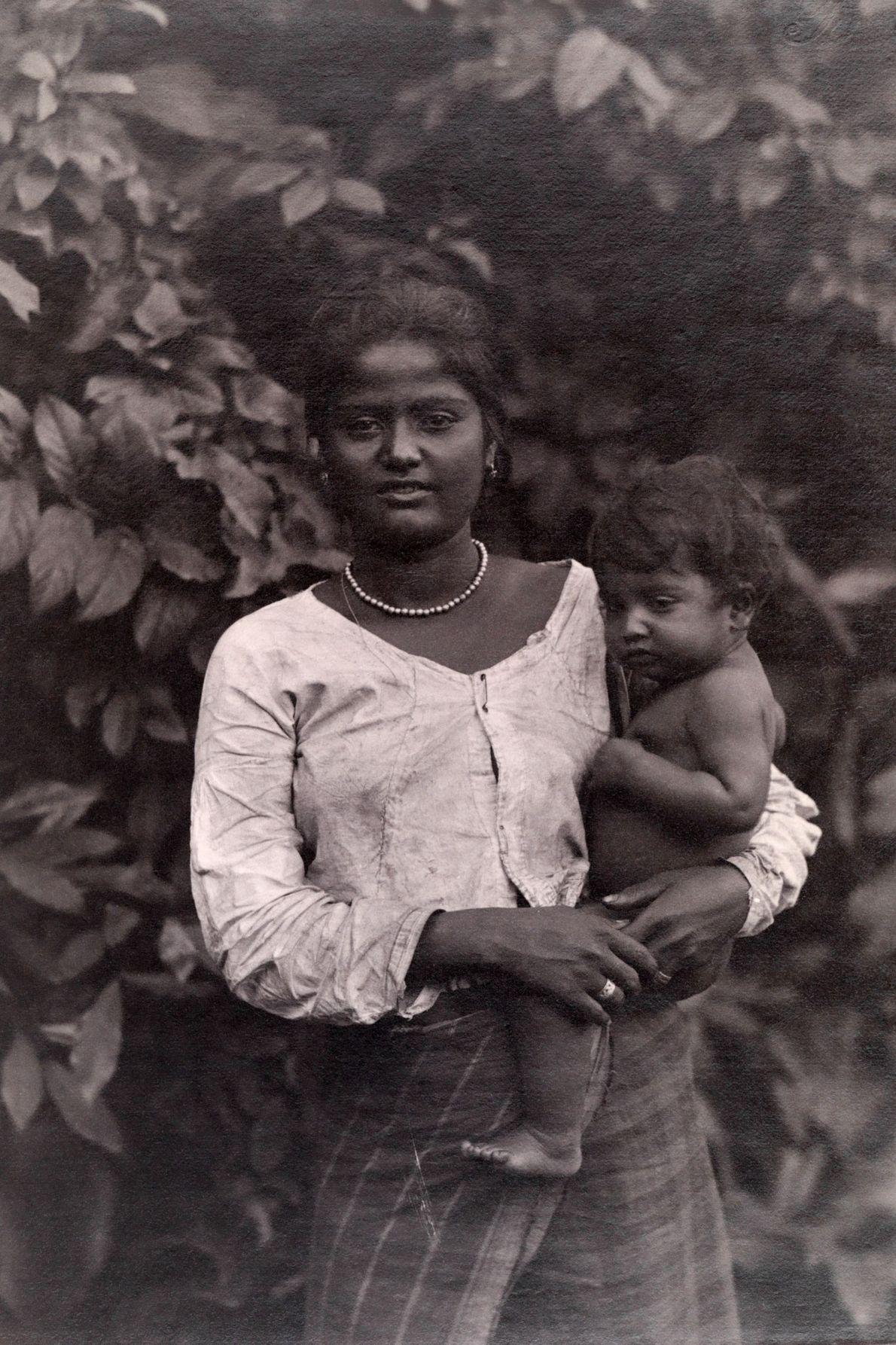 Uma mãe apoia uma criança sobre a anca.