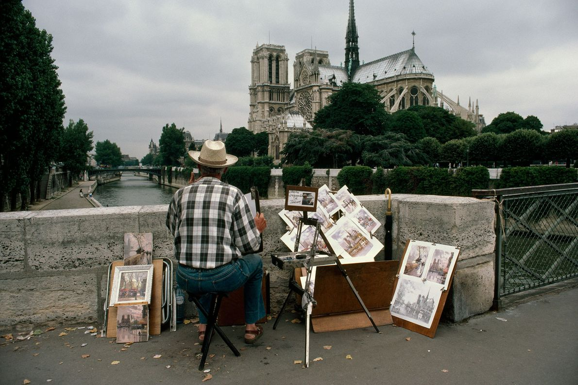 Um artista observa Notre-Dame a partir da Ponte de l'Archevêché.
