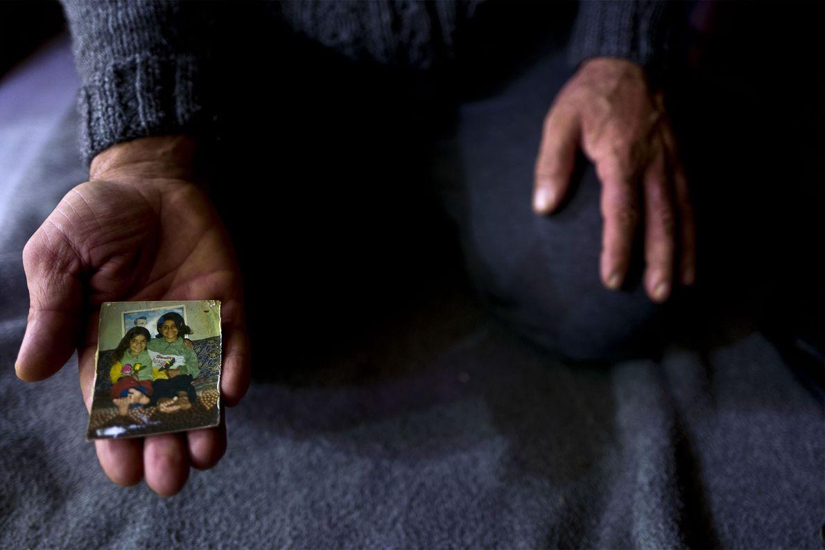 Ibraheem Ghareeb mostra uma fotografia das suas filhas.