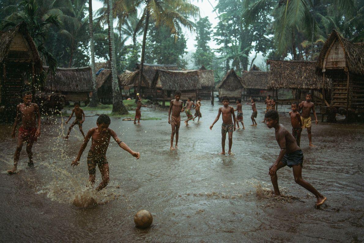 Um grupo de rapazes joga futebol numa aldeia inundada.