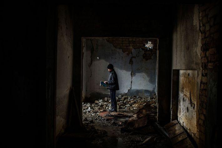 Nikita, 12 anos, no interior de uma escola bombardeada e abandonada em 2014, em Nikishino, na ...