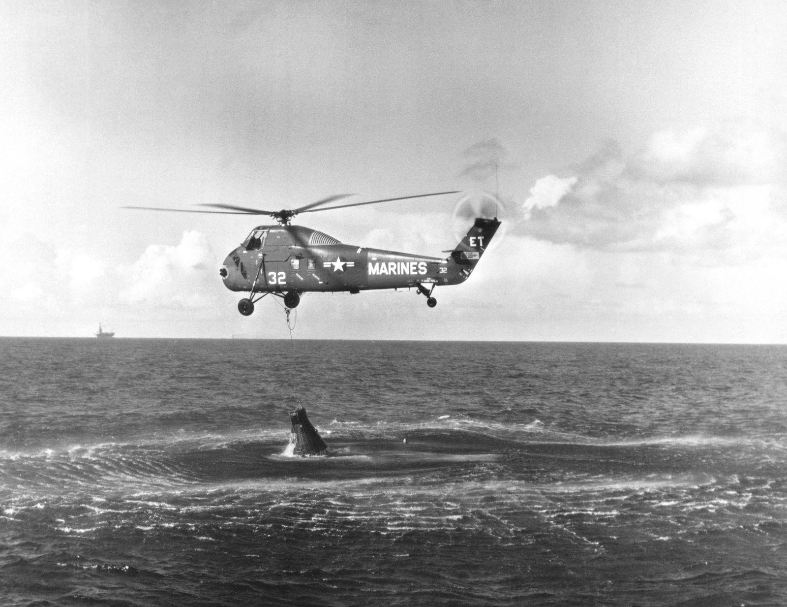 Um helicóptero da Marinha dos EUA tenta içar a Liberty Bell 7 da água depois de ...