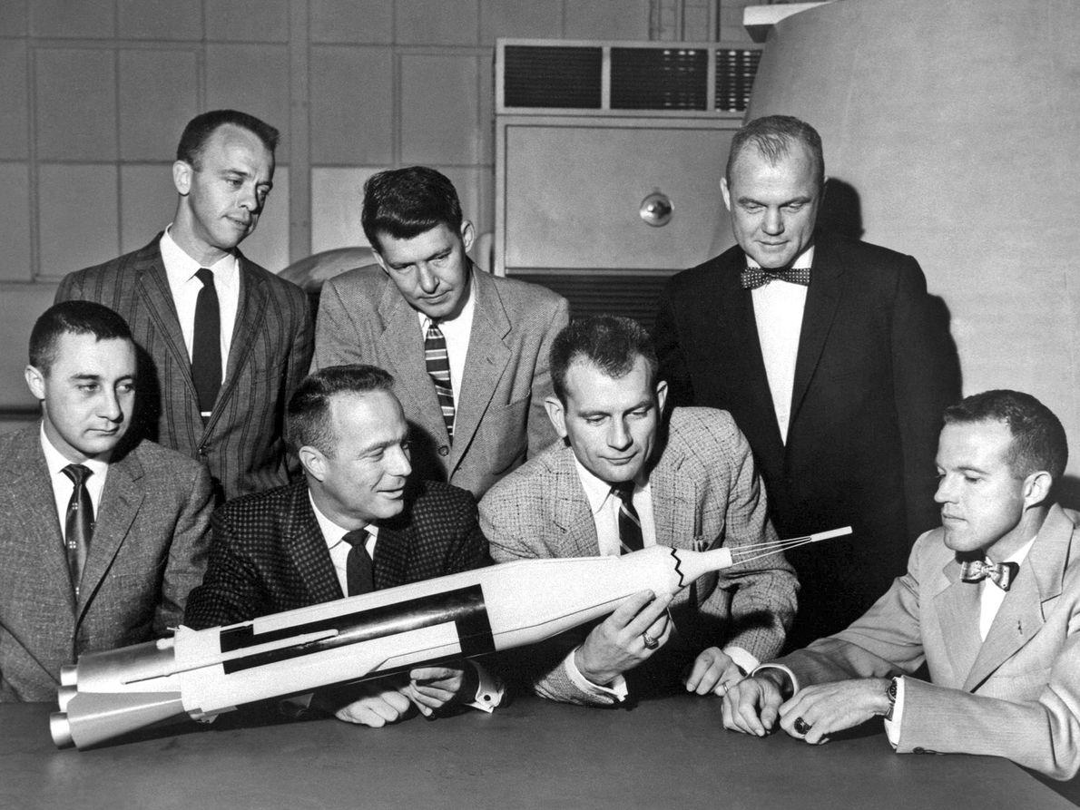 Os astronautas posam com uma maquete do foguetão com a cápsula no nariz. As missões Mercury ...
