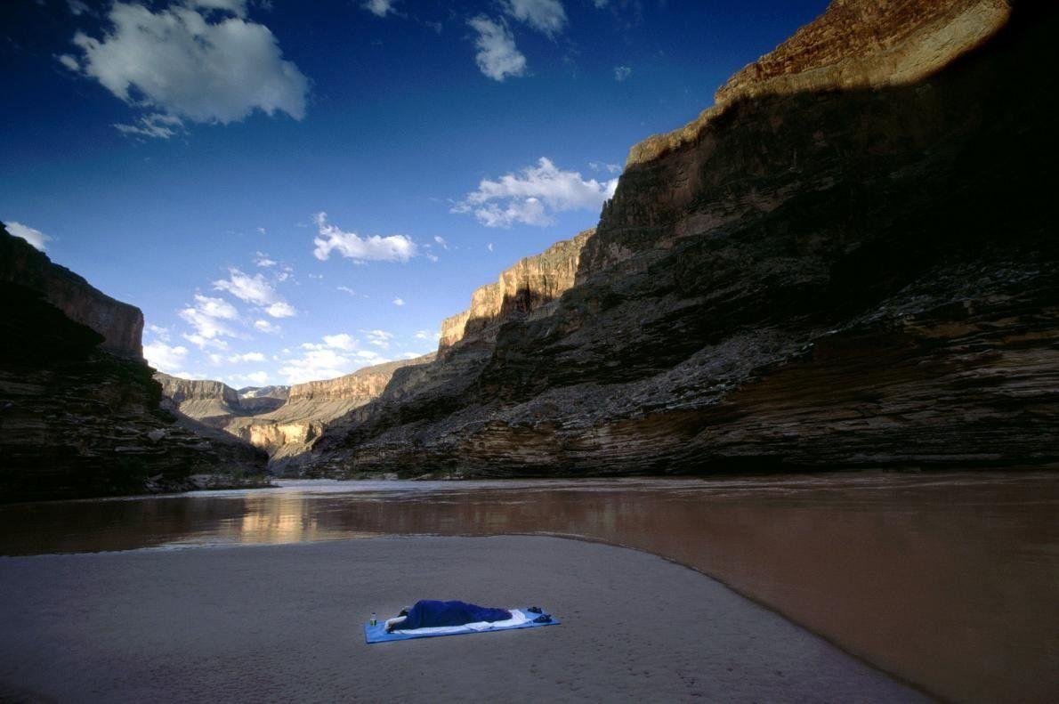 Um explorador solitário dorme num banco de areia na margem do rio Colorado.