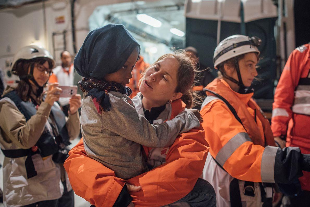 Uma enfermeira canadiana dos Médicos Sem Fronteiras, toma conta de uma criança.