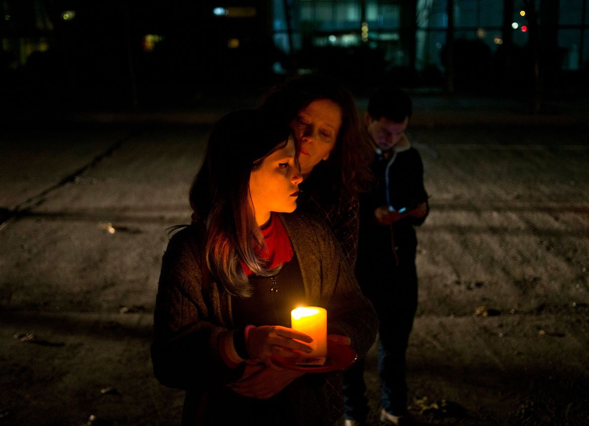 Duas mulheres seguram uma vela durante uma vigília