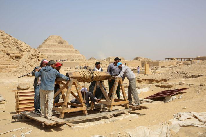 Os trabalhadores usam um guincho manual para transportar ferramentas e outros equipamentos para a oficina de ...