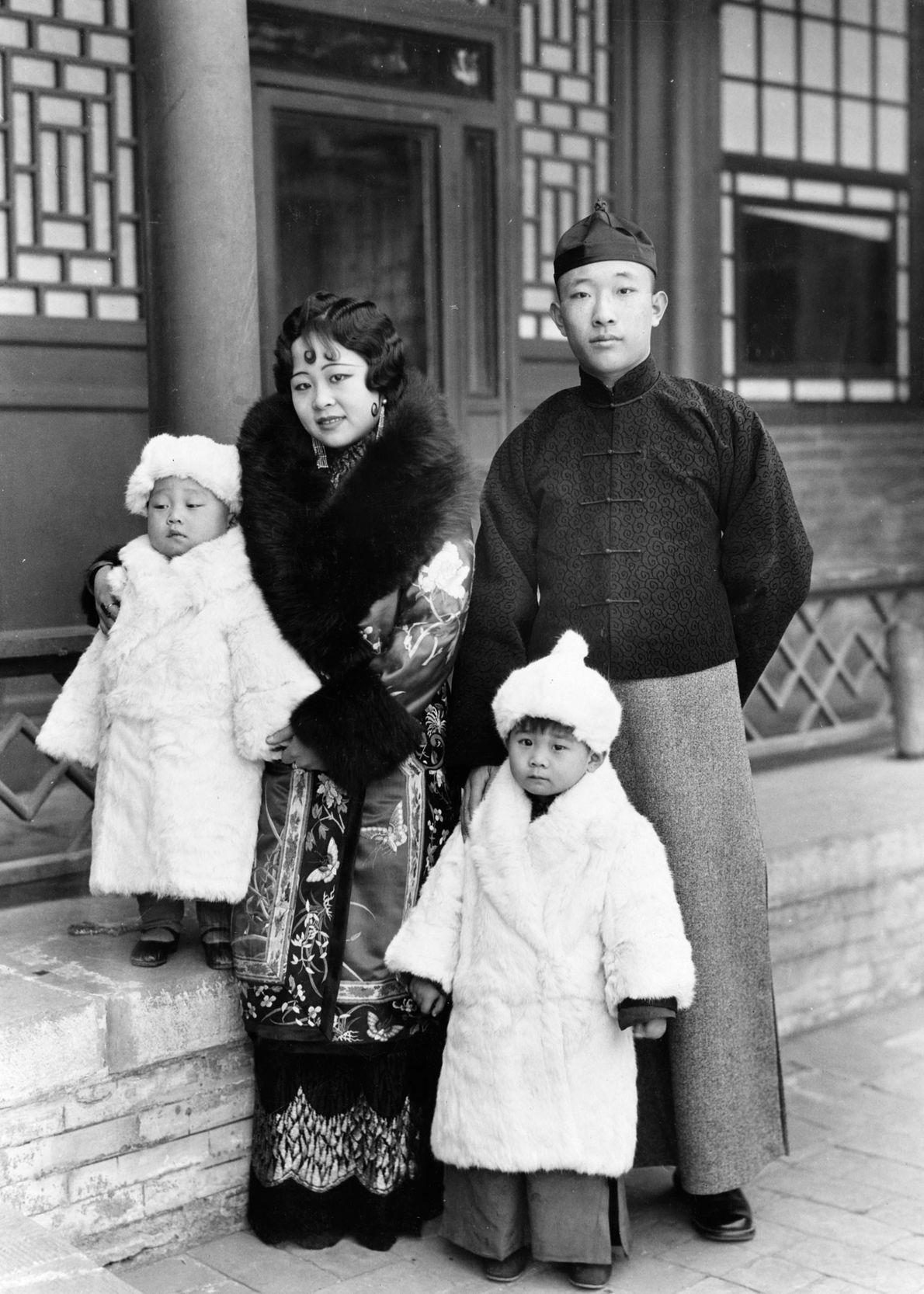 Um príncipe e uma princesa mongóis, na década de 1930, com os seus filhos envoltos em ...