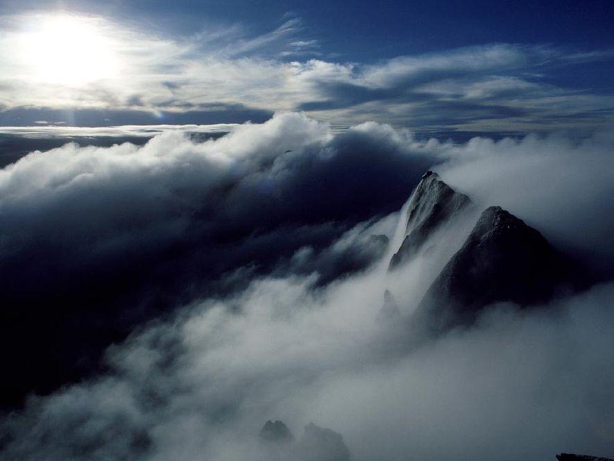 O nevoeiro encobre o cume do monte Kinabalu, na Malásia, uma elevação com 4101 metros de ...