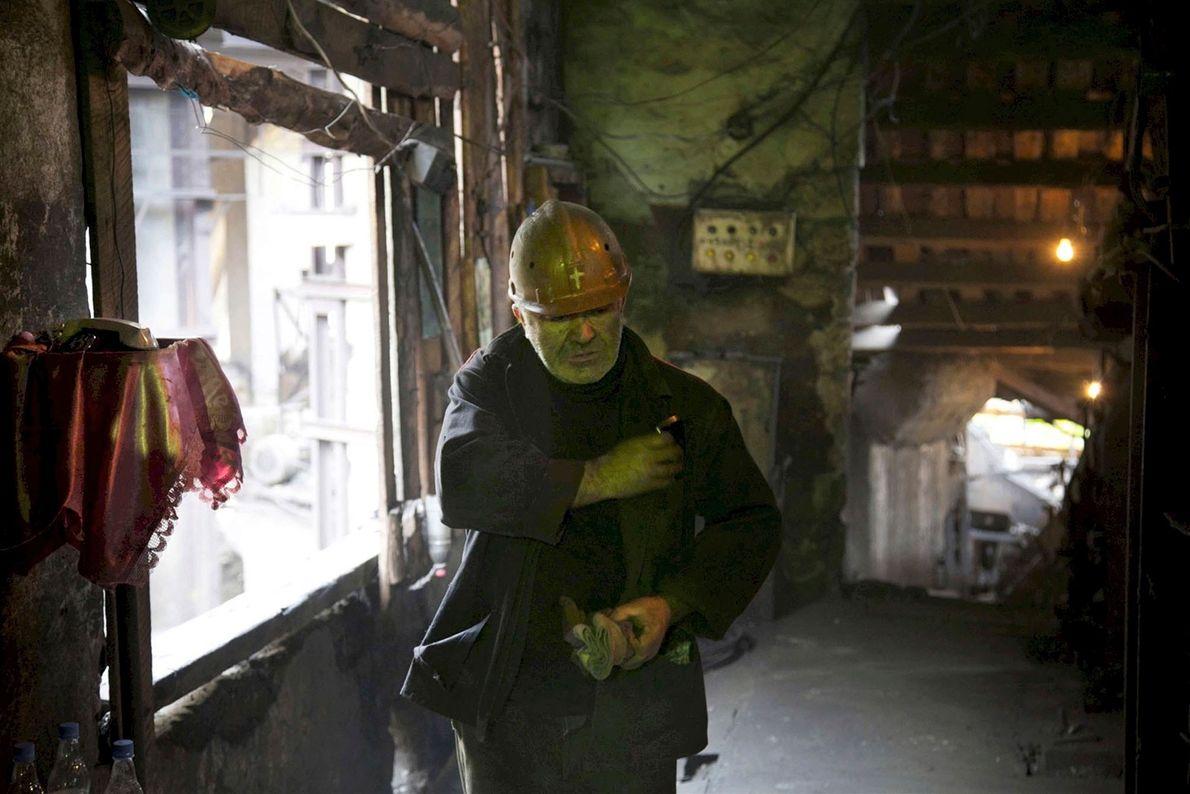Mineiro usa um capacete de segurança gravado com uma cruz