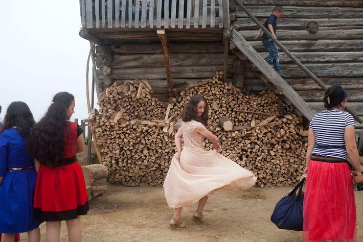 Imagem de uma rapariga a rodar num vestido cor de rosa em frente a uma fogueira