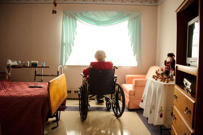 Senhora sentada numa cadeira de rodas em frente à janela