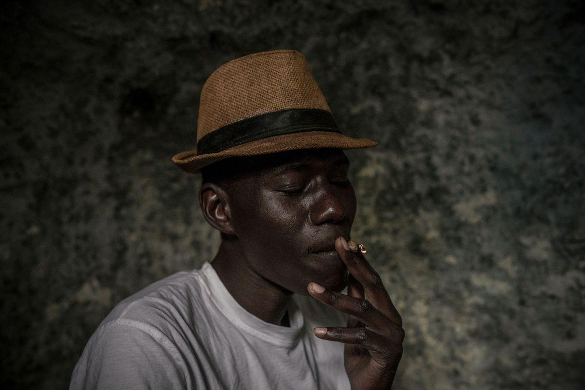 Mbacke, que vive nas grutas por razões económicas, fuma um cigarro no interior da sua casa.