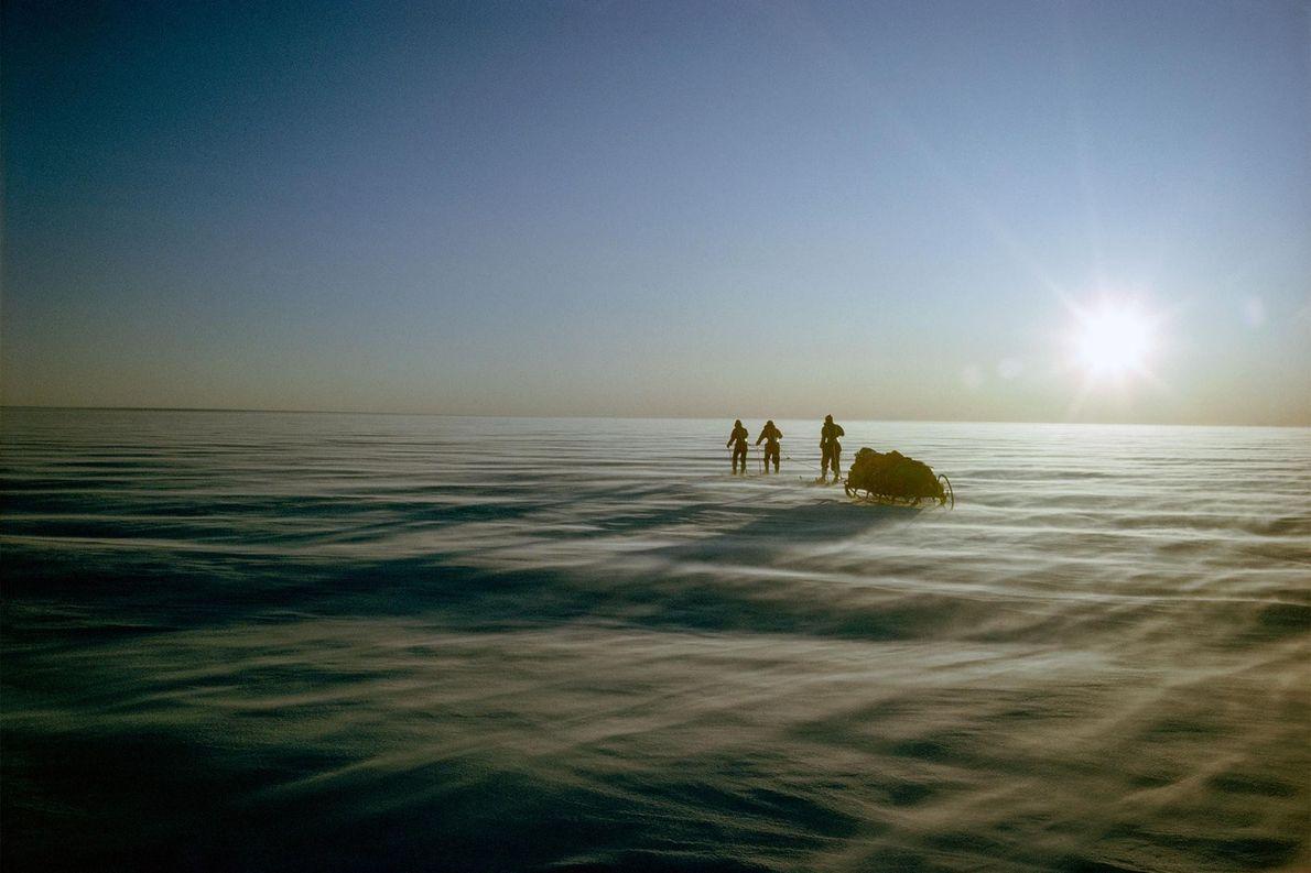 A equipa de expedição puxa o trenó sobre a paisagem gelada da Gronelândia.