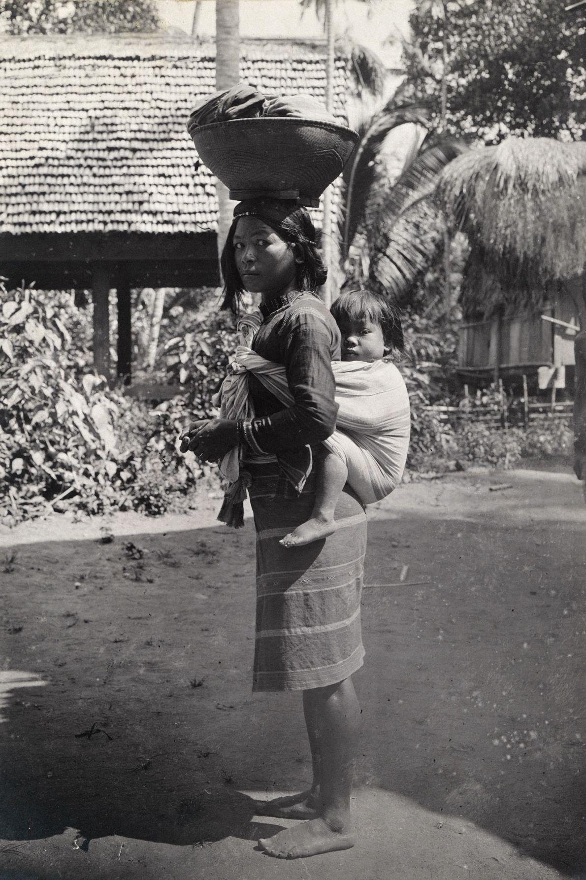 Uma mulher carrega uma criança às costas.