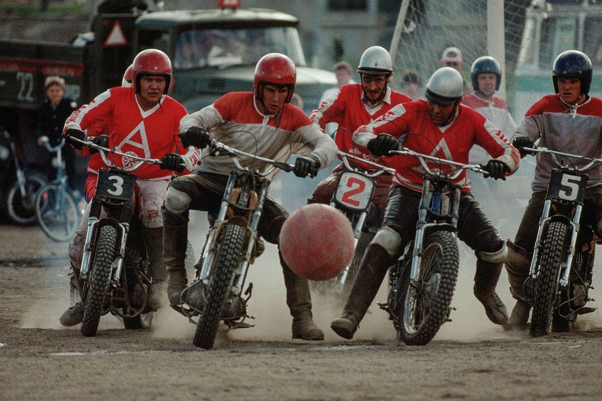 Um grupo de homens sobre motas jogam uma partida de motoball.