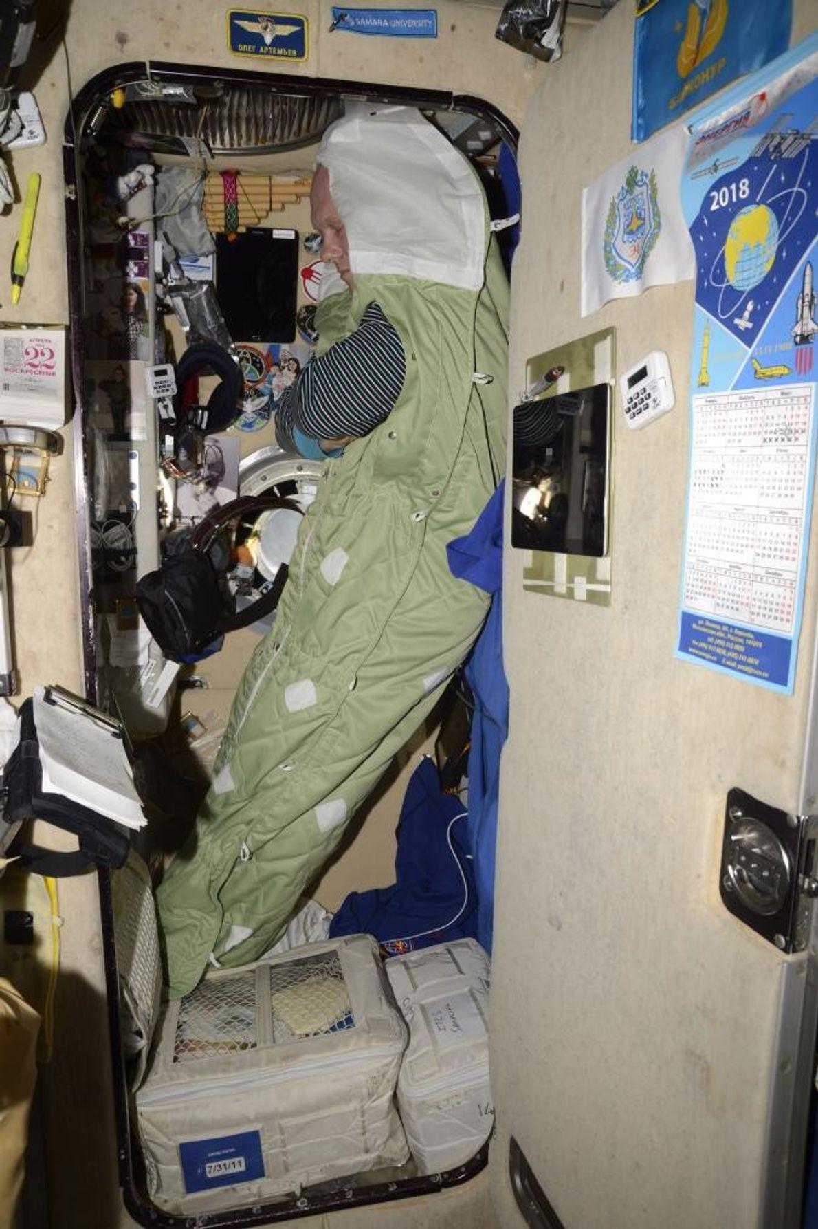 O cosmonauta Oleg Germanovich Artemyev dorme na vertical, com gravidade zero.