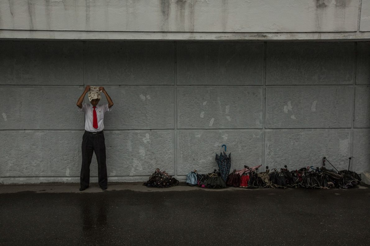 Um homem coloca um lenço sobre a sua cabeça para se proteger da chuva