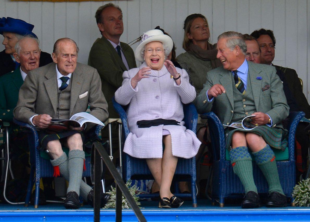 Fotografia do Príncipe Filipe, Rainha Isabel e Príncipe Carlos enquanto aplaudem