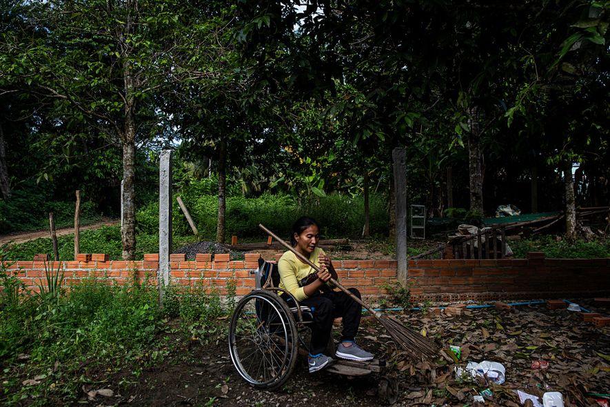 Sieng Sokchan a limpar o jardim da sua casa, em Battambang, no Camboja, onde vive com ...