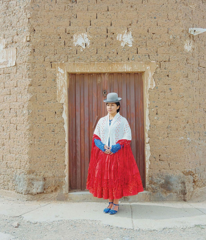 Wara, uma cholita lutadora de 19 anos, posa em frente de um edifício em El Alto.
