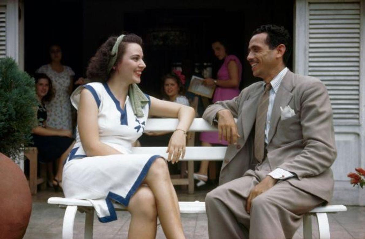 Duas pessoas conversam sentadas num banco durante uma festa ao ar livre.