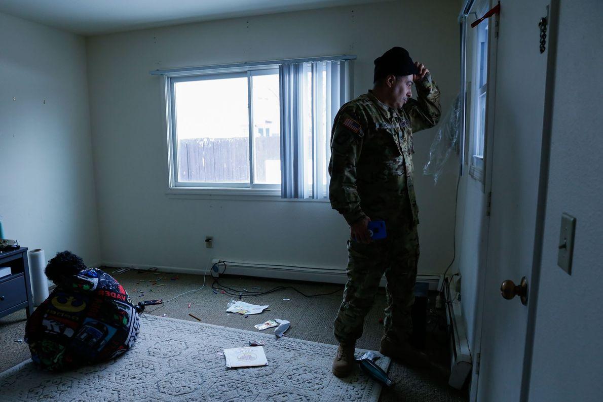 O pai de Lola olha pela janela de uma casa vazia.