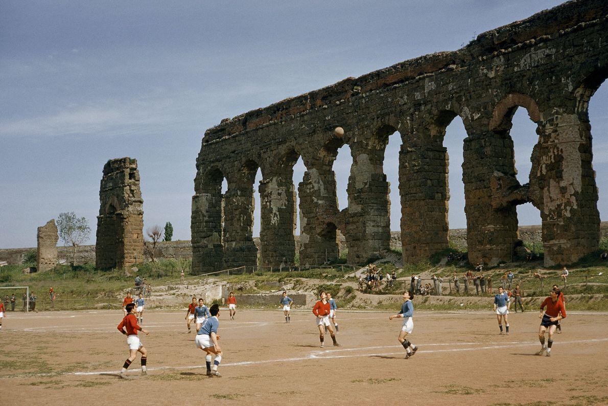 Um grupo de rapazes joga futebol junto aos arcos de um antigo aqueduto em Roma.