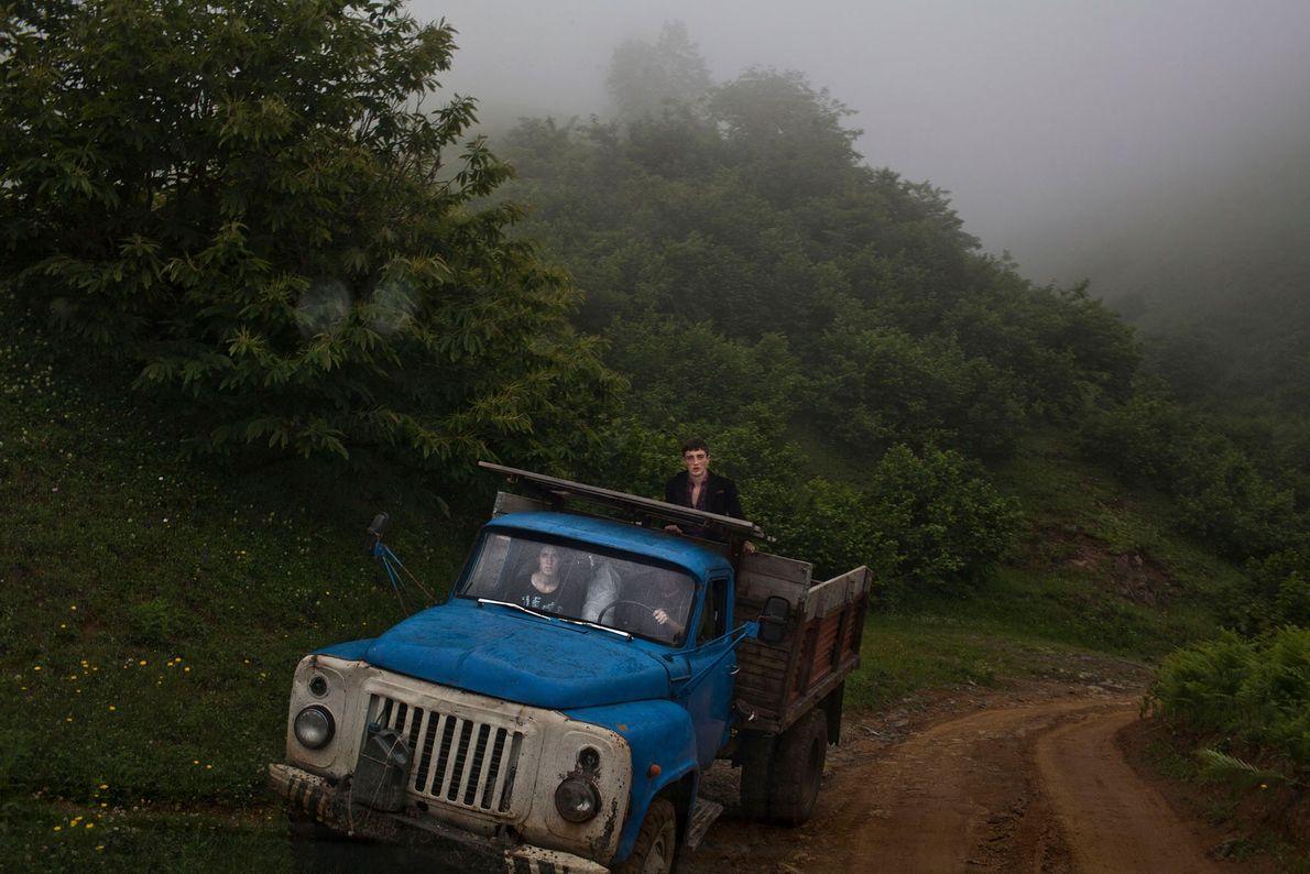Imagem de uma carrinha azul a andar numa estrada de terra