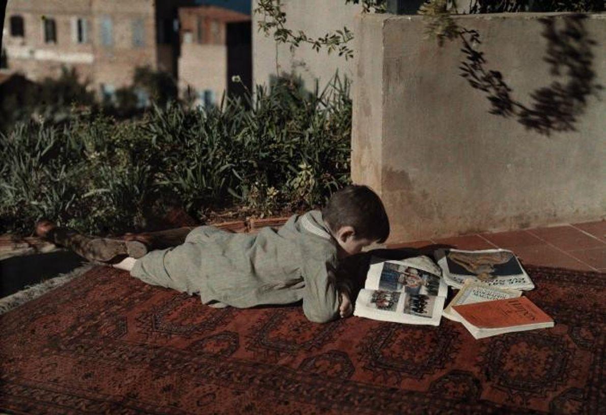 Um rapaz lê estendido sobre um tapete em Beirute, em 1927.