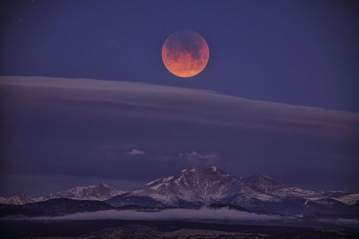 Apesar das nuvens, o eclipse lunar de uma superlua azul de sangue ainda conseguiu espreitar sobre ...