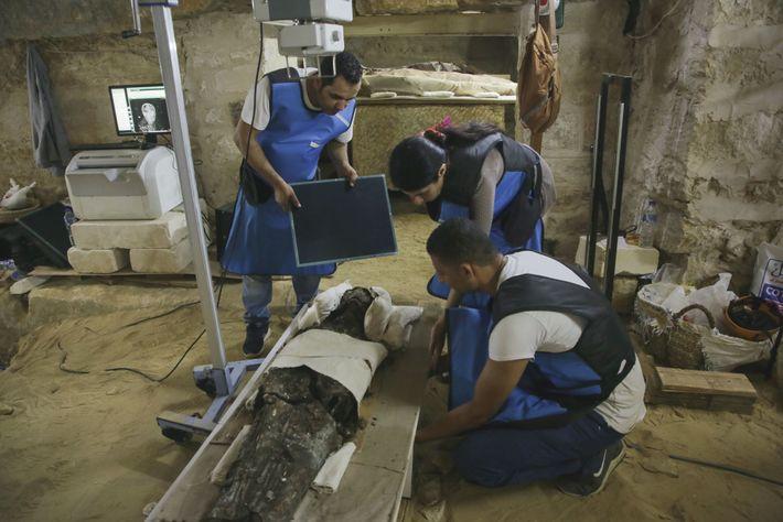 A paleorradiologista Sahar Saleem (entre dois técnicos) usa uma unidade móvel de raios-x para revelar os ...