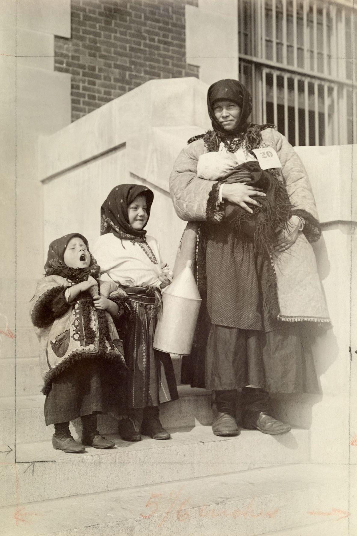 Uma imigrante russa posa diante de uma habitação com os seus três filhos.