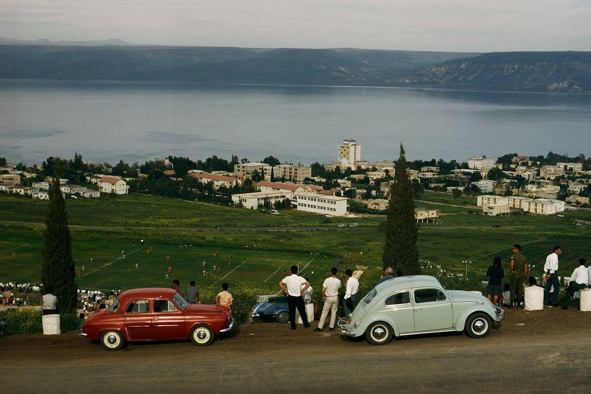 Turistas conduzem até ao cimo de uma encosta, onde estacionam para assistir a uma partida de ...