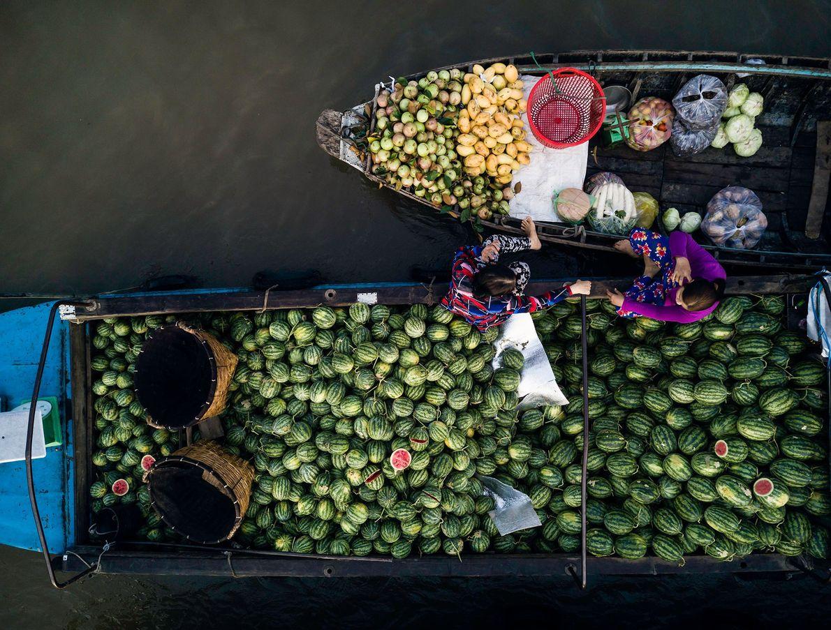 Comerciantes a conversar enquanto aguardam pelos clientes, no mercado flutuante de Phong Dien, no Delta do ...