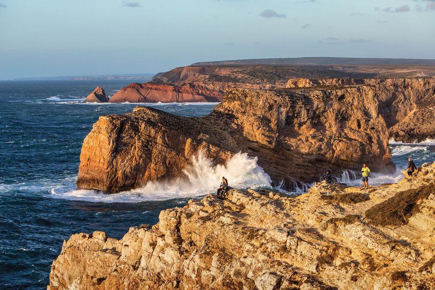 Viajantes a desfrutar de banhos de sol, no cabo de São Vicente, em Sagres, o ponto ...