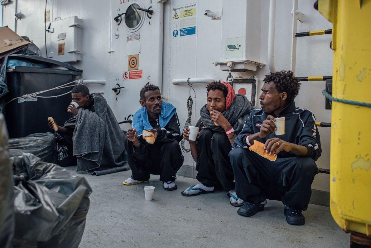 Os refugiados com roupas novas, cobertores, água e comida.