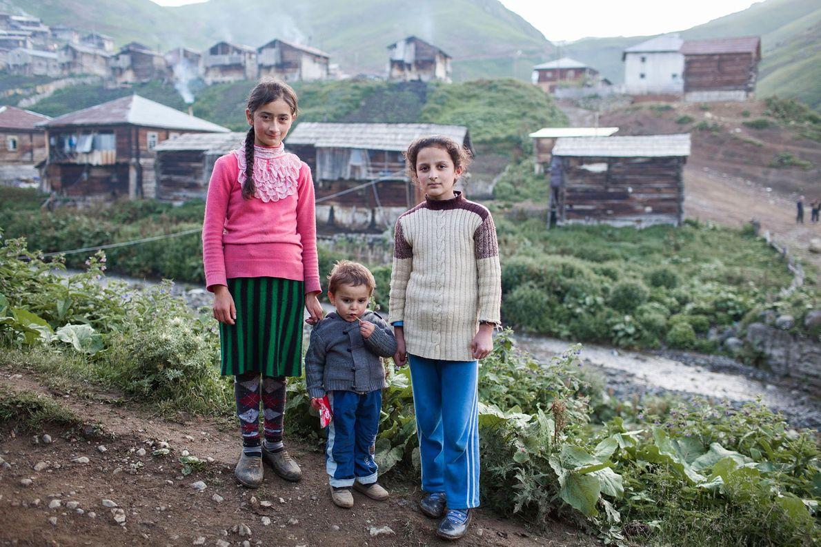 Imagem de três crianças na frente de uma aldeia