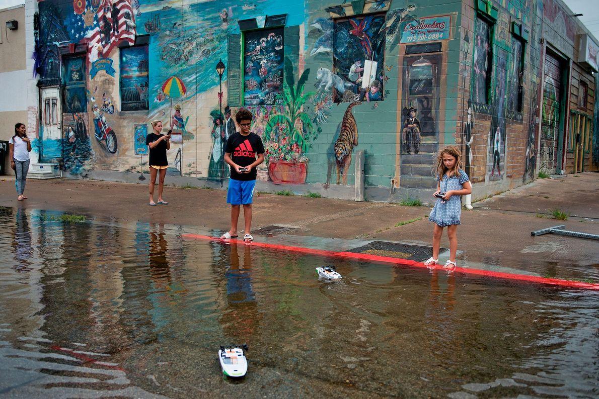 Crianças brincam numa estrada inundada