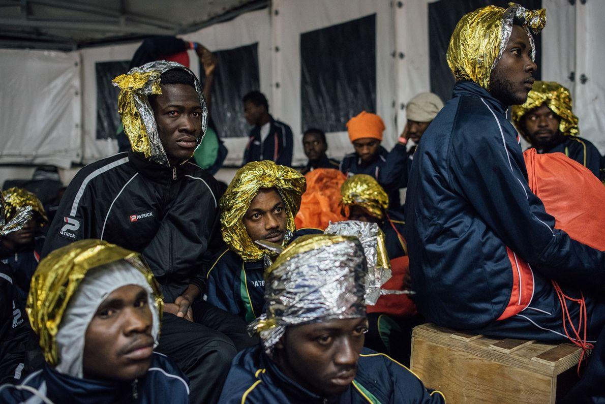 Os refugiados da África Ocidental envolvem a cabeça em mantas térmicas.