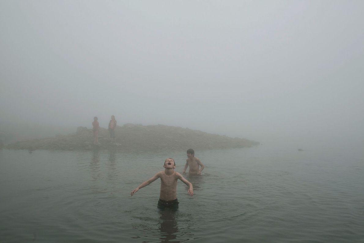 Imagem de crianças a brincarem num lago