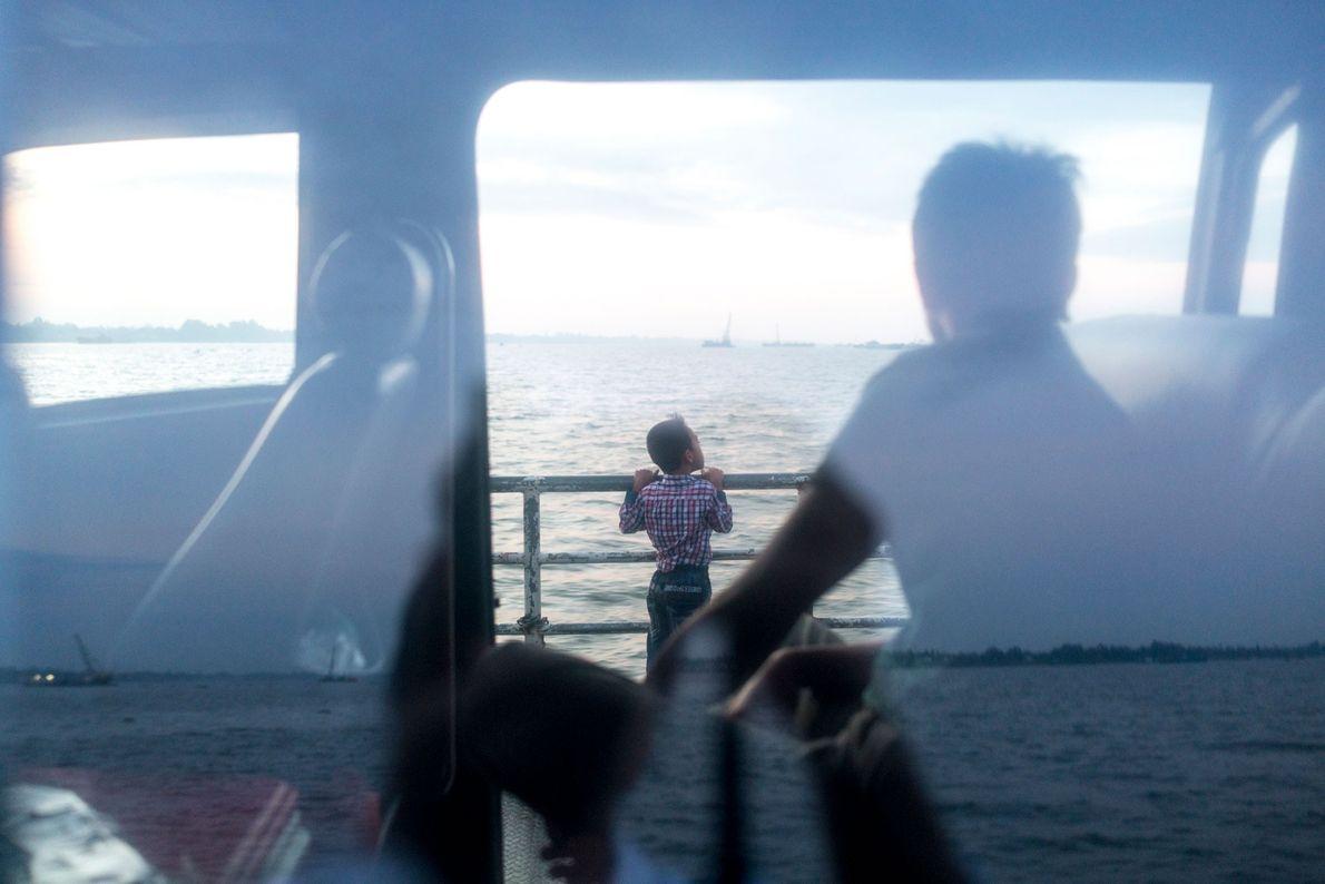 Passageiros atravessam o rio Tien num ferry