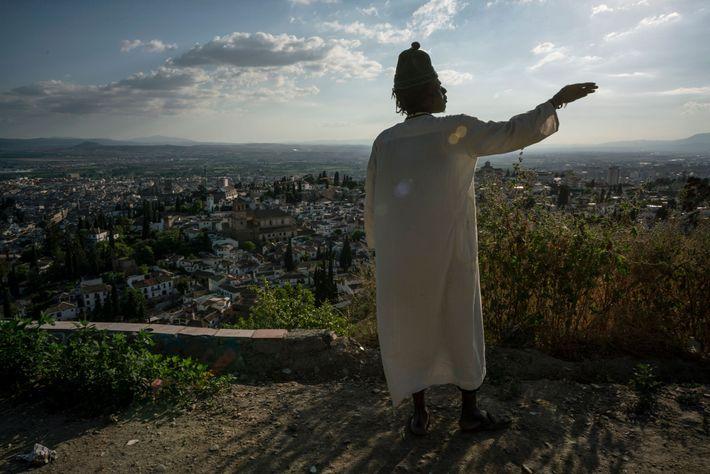 Mbacke contempla o horizonte sobre a cidade de Granada no espaço em frente à sua gruta. ...